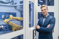 Portrait of a confident businessman in front of a robot in a modern factory - DIGF07707