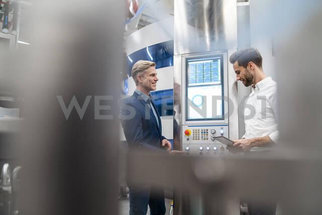 Two businessmen talking in a modern factory - DIGF07710 - Daniel Ingold/Westend61