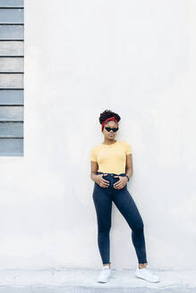Young woman wearing hair-band and sunglasses leaning against white wall - SODF00002