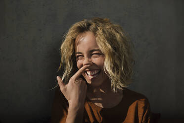 Portrait of laughing blond woman pulling funny faces - GCF00266