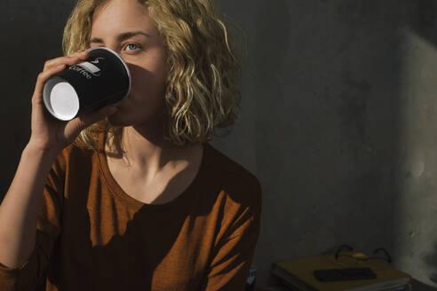Stundentin trinkt Kaffee, Wohnung, Deutschland, Berlin, Studentin im WG-Zimmer - GCF00269
