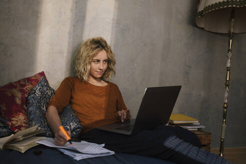 Portrait of blond student sitting on bed working on laptop - GCF00287