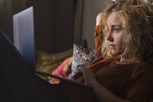 Portrait of blond young woman lying on bed using laptop - GCF00293
