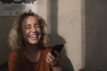 Portrait of laughing young woman with cell phone - GCF00302