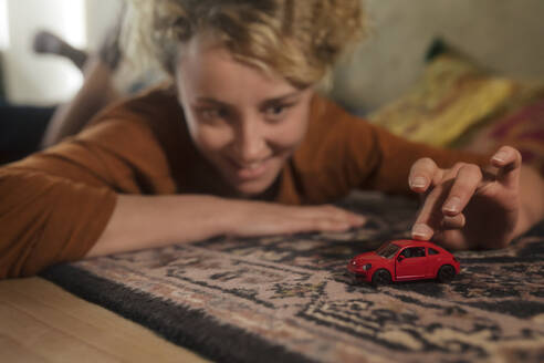 Young woman lying on carpet playing with red toy car - GCF00308