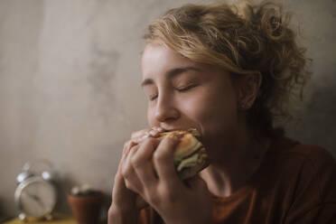 Portrait of young woman eating Hamburger - GCF00311