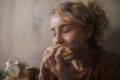 junge Frau isst Burger, Wohnung, Deutschland, Berlin, Studentin im WG-Zimmer - GCF00311