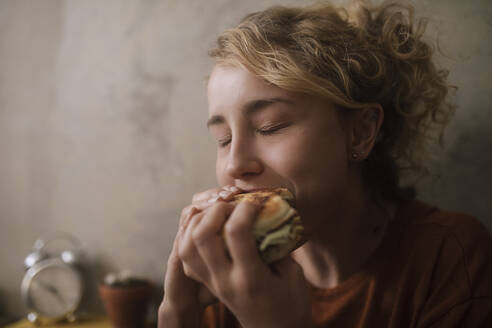 Portrait of young woman eating Hamburger - GCF00311