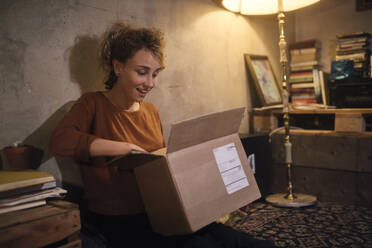 Amazed young woman unpacking parcel at home - GCF00314