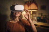 Young woman using Virtual Reality Glasses at home - GCF00317