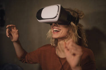Laughing young woman using Virtual Reality Glasses at home - GCF00320