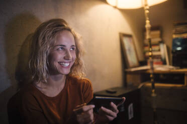 Portrait of laughing young woman using smartphone at home - GCF00323