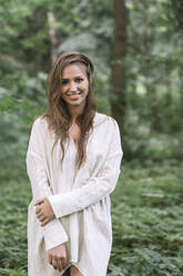 Portrait of a smiling young woman in a forest - AHSF00591