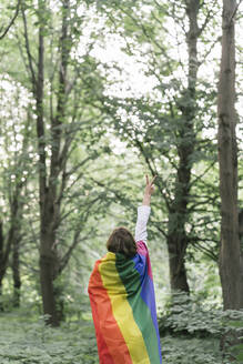 Rear view of a woman covered in a rainbow flag showing the victory sign - AHSF00594