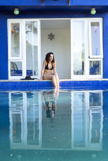 Mixed race woman reflected in swimming pool - BLEF10292