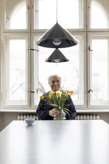 Smiling senior man with bunch of flowers sitting at table at home - GUSF02039
