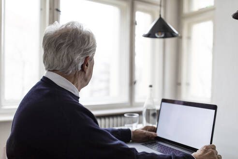 Senior man using laptop on table at home - GUSF02048