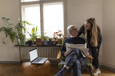 Happy young woman and senior man with newspaper at home - GUSF02057