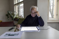Senior man using tablet with architectural plan - GUSF02063