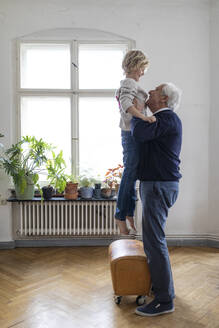 Grandfather lifting up grandson at home - GUSF02075