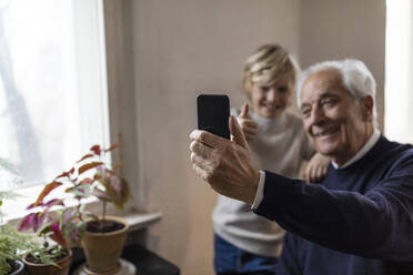 Happy grandfather and grandson taking a selfie at home - GUSF02084