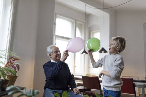 Happy grandfather and grandson playing with balloons at home - GUSF02087