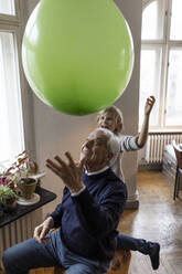 Happy grandfather and grandson playing with balloon at home - GUSF02090
