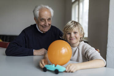 Happy grandfather and grandson playing with toy car and balloon at home - GUSF02099