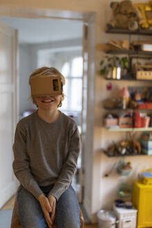 Boy sitting on buck in his room at home wearing cardboard VR glasses - GUSF02126
