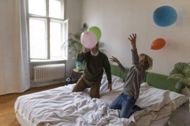 Happy grandfather and grandson playing with balloons on bed at home - GUSF02129