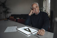Smiling senior man using tablet with architectural plan - GUSF02144