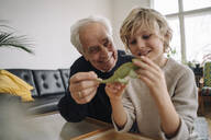 Happy grandfather and grandson playing with toy chameleon at home - GUSF02153