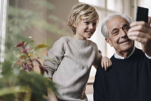Happy grandfather and grandson taking a selfie at home - GUSF02162