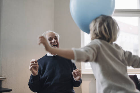 Happy grandfather and grandson playing with balloons at home - GUSF02165