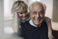 Portrait of happy grandfather and grandson at home - GUSF02168