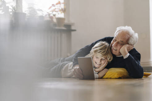 Happy grandfather and grandson lying on the floor at home using a tablet - GUSF02183