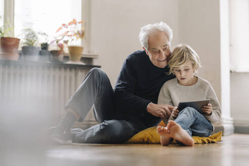 Grandfather and grandson sitting on the floor at home using a tablet - GUSF02186