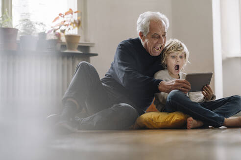 Screaming grandfather and grandson sitting on the floor at home using a tablet - GUSF02189