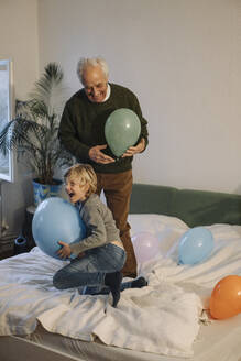 Happy grandfather and grandson playing with balloons on bed at home - GUSF02207