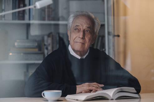 Senior man reading book at home - GUSF02216