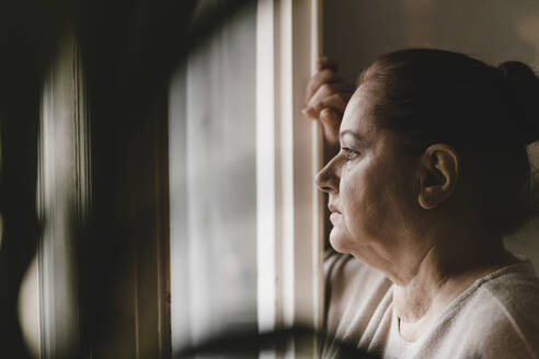 Serious senior woman looking out of window at home - GUSF02222