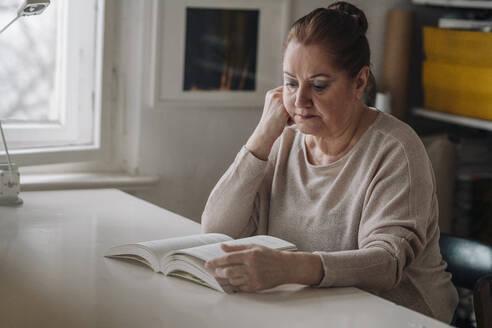Senior woman reading book at home - GUSF02228