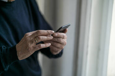 Close-up of senior man using cell phone at home - GUSF02240