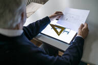 Senior man using tablet with architectural plan - GUSF02246
