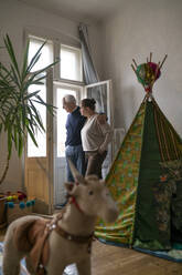 Senior couple standing in children's room looking out of window - GUSF02258