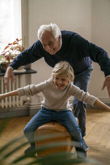 Happy grandfather and grandson playing with buck at home - GUSF02264
