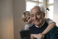 Happy grandson hugging grandfather with cell phone at home - GUSF02267
