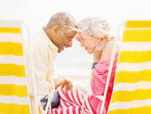 Older couple sitting in lawn chairs on beach - BLEF10435