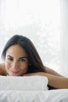 Caucasian woman laying on massage table - BLEF10444