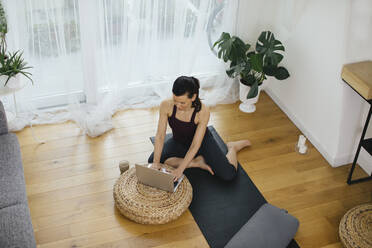 Woman sitting on gym mat at home using laptop - SODF00016